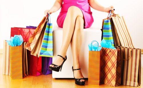 Дівчина сидить з купою пакетів з покупками
