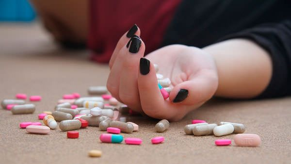 Дівчина приймає таблетки щоб вилікувати депресію